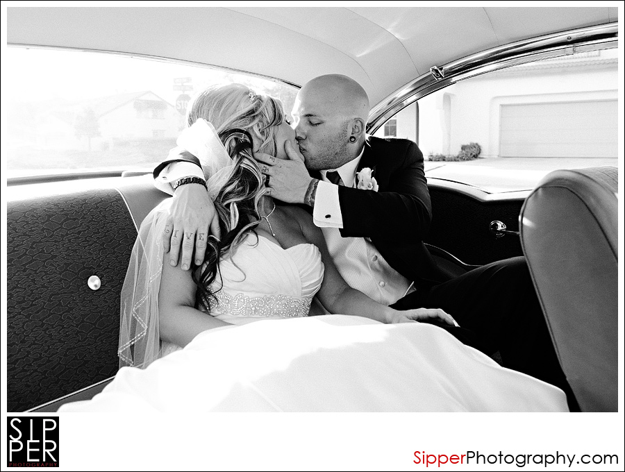 Wedding Couple kissing in the backseat of a 57 chevy