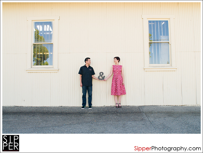 Engagement portrait with couple and ampersand sign