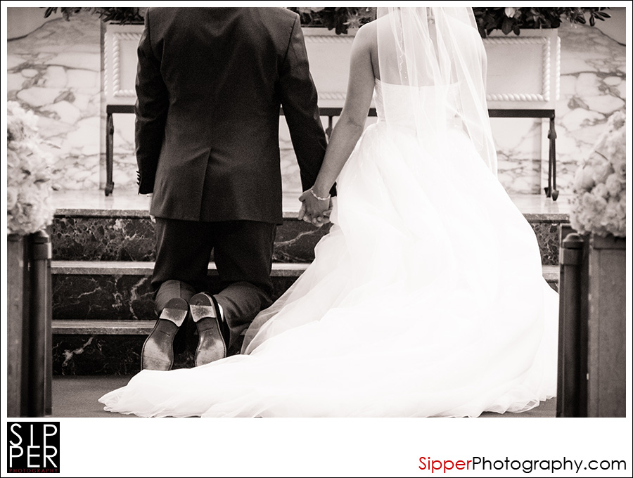 Couple kneeling during wedding ceremony at Our Lady of Mount Carmel Catholic Church