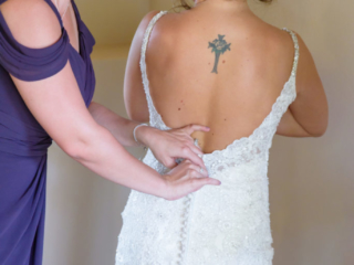 Bride's Sister helps her get ready by buttoning her wedding dress