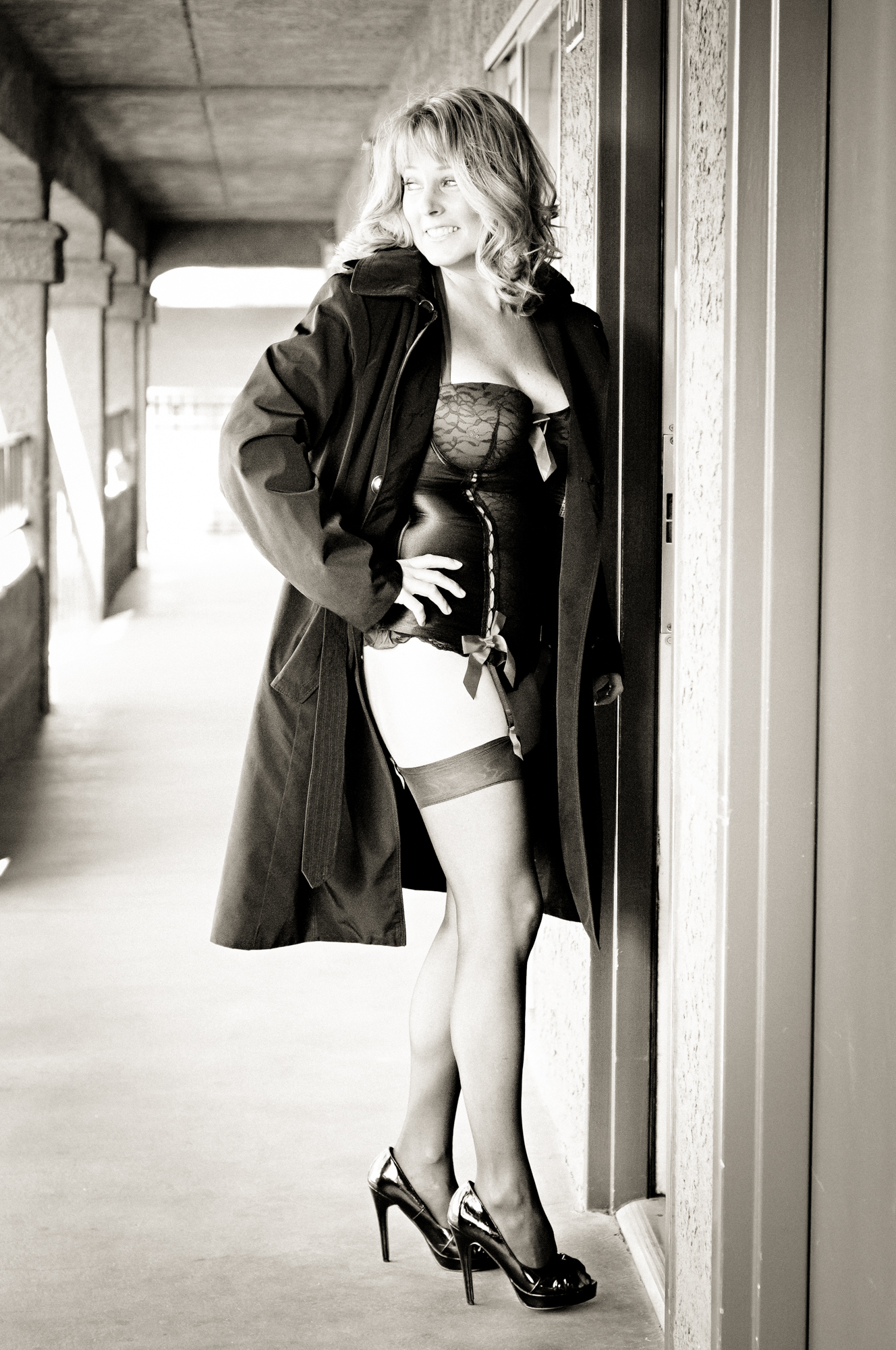 This photo is of a mature woman stepping into a hotel room as part of a boudoir photography session by Dana Sipper. Classic lingerie and a trench coat add to the sexiness of the photo.