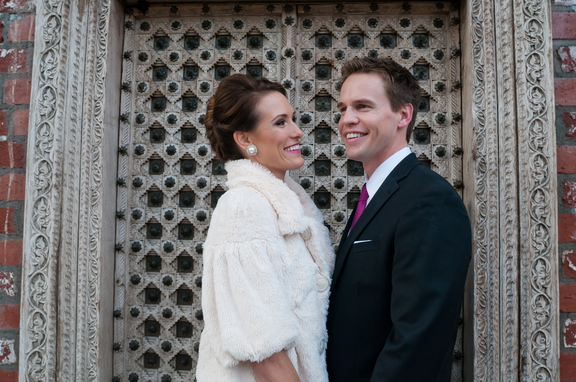 This typical South Orange County couple decided to have their engagement photos in front of a gorgeous iron door located in downtown Laguna Beach. The woman is wearing a vintage furry overcoat while the man has opted for a classic black suit with purple tie, matching the woman's lipstick.
