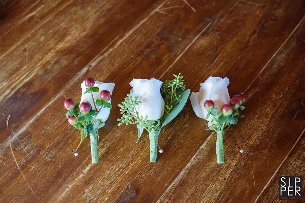Boutonnieres for the groom and his groomsman of white roses set against a weathered wood table.