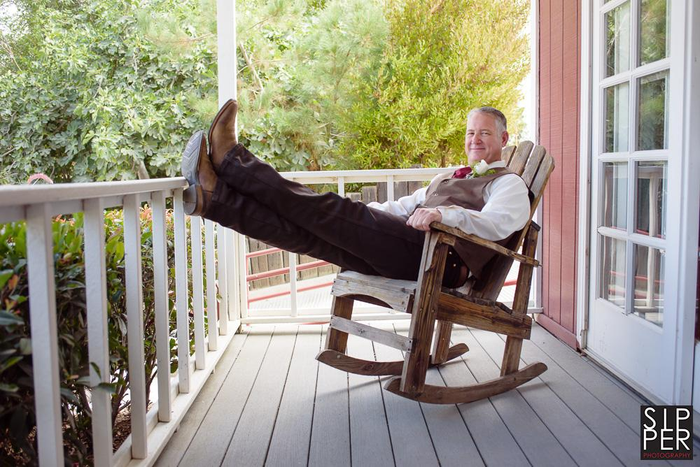 A relaxed modern portrait of the groom kicking back in a rocking chair on the front porch of the Red Horse Barn's groom's room.