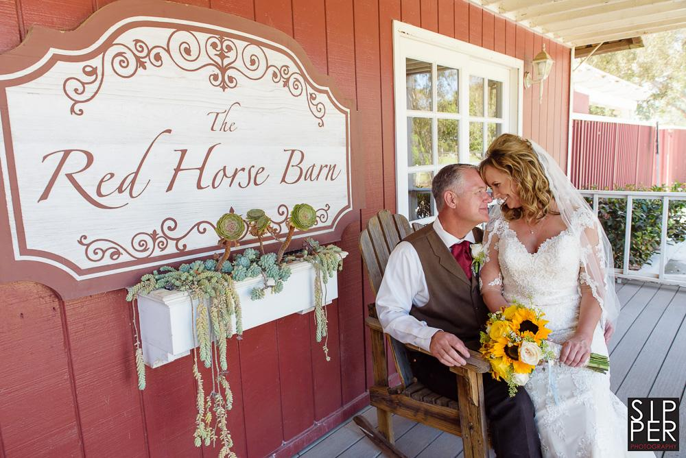 A photo of a wedding couple in front of the sign for the Red Horse Barn. This couple celebrated their day in fashion with a rustic, country themed affair on the back lawn while taking their photos over the expansive propert that the Red Hose Barn has access to.
