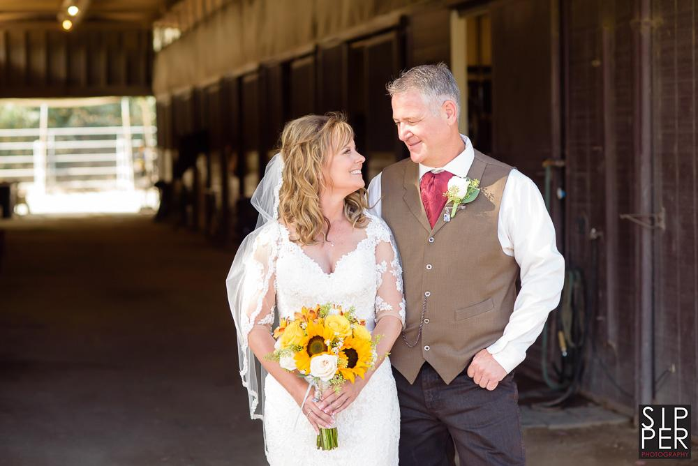 When you have access to a horse barn for a wedding you use it. Here the lovely bridal couple pose in front of horse stalls at the Hunting Beach Equestrian Center