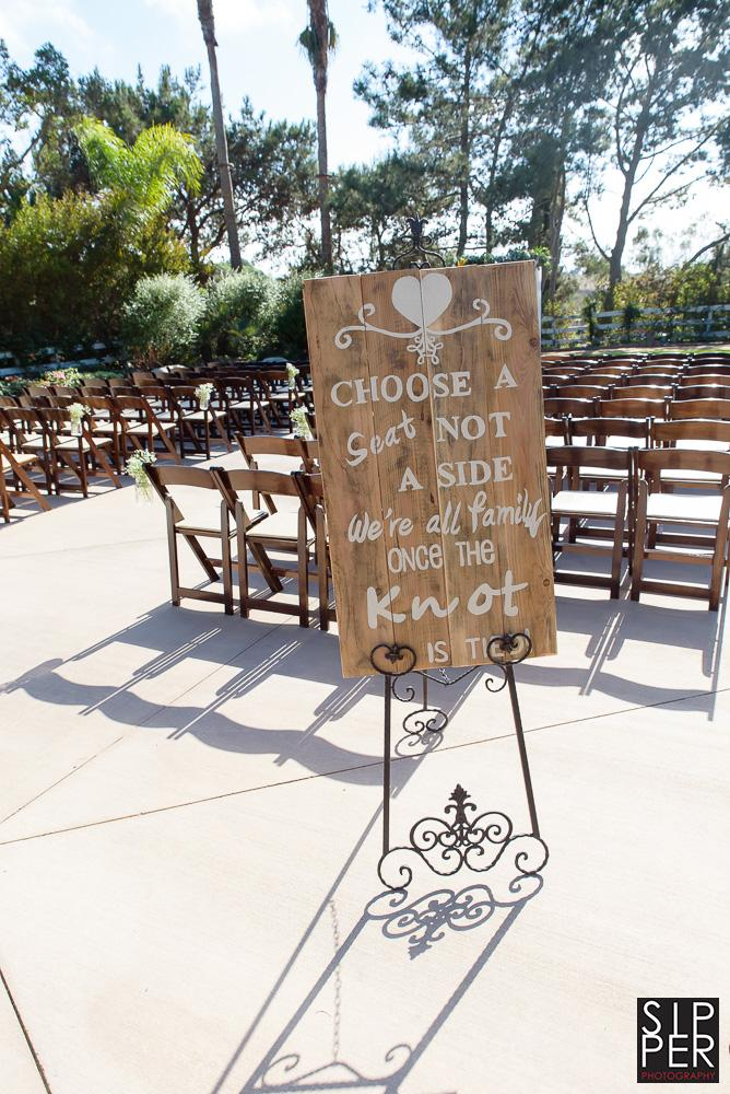 "This is a picture of a sign telling guests to ""Pick a seat, not a side"""