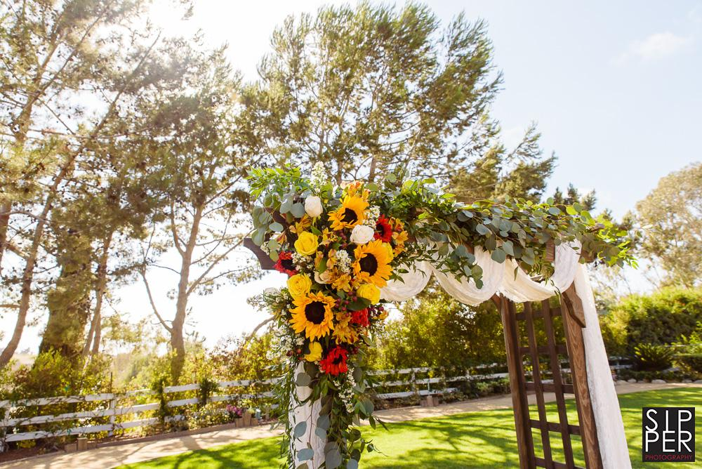 A backlit photo of a ceremony arch draped with sunflowers and tulle material provided by Melia Carlson of Laguna Beach flowers.