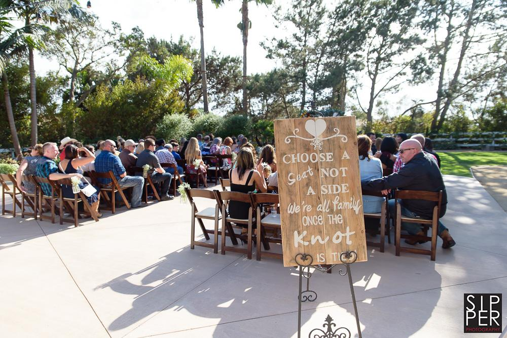 Choose a seat, not a side is written on the sign behind the wedding ceremony seating area of this beautiful outdoor wedding in Huntington Beach, CA. This is a great new tradition of blending multiple families into one.