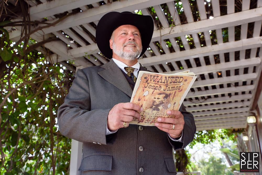 This is a photo of an old west minister at a country themed wedding. He is holding a wanted poster of Jesse James and carried both a gun and a whiskey flask to the ceremony.