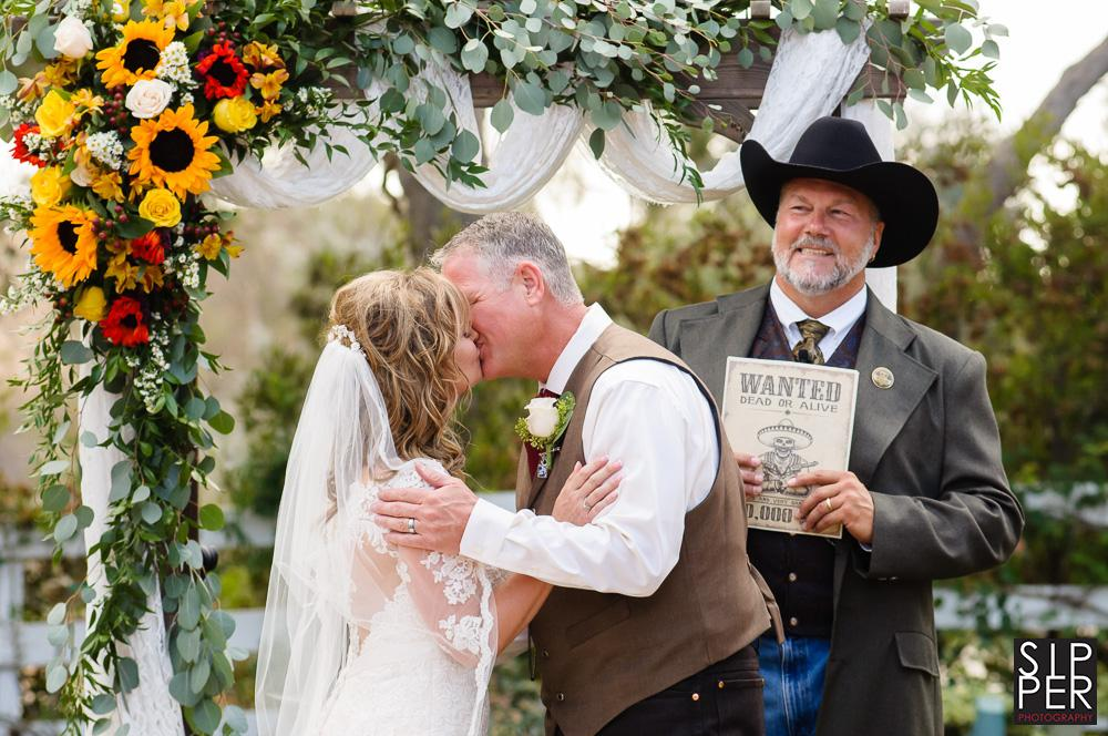 The first kiss is a wonderful wedding tradition that takes place at the end of the ceremony. This rustic service came complete with an old west inspired minister, complete with Stetson cowboy hat, wanted sign and long trench coat similar to Wyatt Earp and lawmen of the old west.