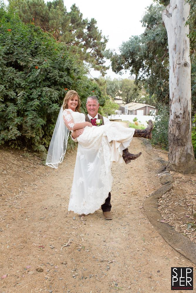 On a back trail of the Red Horse Barn, the groom carries his bride.