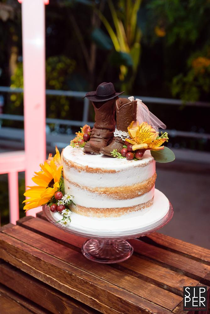 A Naked cake is a modern twist on a traditional wedding cake. This one features chocolate boots on top and some sunflowers on the side of the cake.