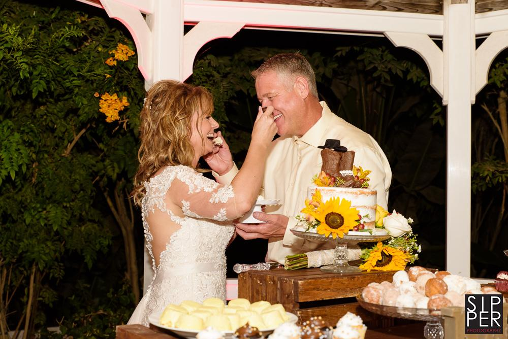 A photo of a bride and groom feeding each other cake at a traditional cake cutting event at an outdoor wedding